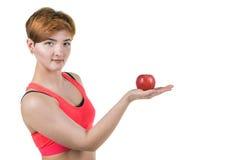健康生活方式,健康吃 女孩拿着在她的手上的一个红色苹果,在白色被隔绝的背景 水平的框架 免版税库存照片