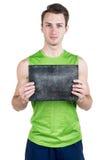 健康生活方式 一个英俊的人的画象有一块空白的牌的写的,在运动服,被隔绝在白色背景, l 库存图片