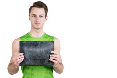 健康生活方式 一个英俊的人的画象有一块空白的牌的写的,在运动服,被隔绝在白色背景, l 库存照片