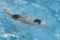 健康男孩爬泳在游泳池游泳 免版税库存照片