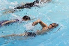 健康男孩爬泳在游泳池游泳 免版税图库摄影
