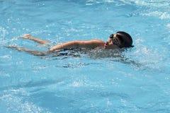 健康男孩爬泳在游泳池游泳 免版税库存图片