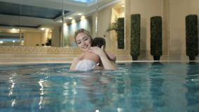 健康的系列 在水池的母亲教的女婴游泳 影视素材