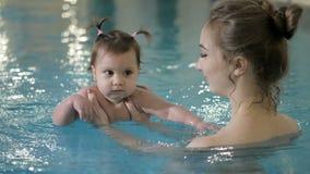 健康的系列 在水池的母亲教的女婴游泳 股票录像