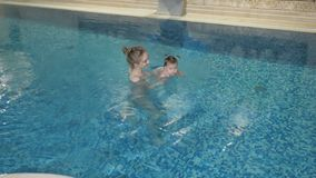 健康的系列 在水池的母亲教的女婴游泳 股票视频