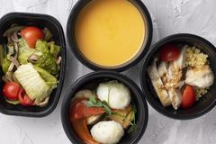 健康的适当的营养在塑胶容器、浓豌豆汤、蒸的肉和菜 免版税库存照片