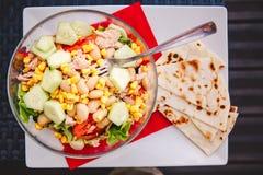 健康的食物 与金枪鱼、莴苣、豆、玉米、黄瓜和蕃茄的鲜美鱼沙拉在有叉子的一块板材 顶视图 免版税图库摄影