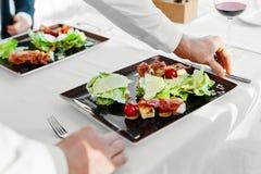 健康的食物 吃膳食的夫妇凯萨色拉在餐馆 免版税库存照片