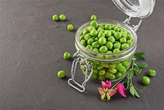 健康的食物 在开放玻璃瓶子的新鲜的绿豆有香豌豆花桃红色花的  库存照片