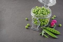 健康的食物 在开放玻璃瓶子的新鲜的绿豆有香豌豆花桃红色花的  库存图片