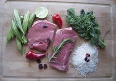 健康的食物 牛肉和绿色和红色菜在木桌上与钢刀子 免版税库存图片