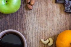 健康的食物 苹果、桔子、坚果、黑暗的巧克力和黑coffe 免版税库存图片