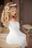健康的头发 有长的白肤金发的卷曲hai的美丽的微笑的新娘 免版税库存图片