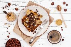 健康秋天和冬天早餐素食主义者香草法式多士用焦糖的香蕉、未加工的黑暗的巧克力和榛子涂黄油 免版税库存照片