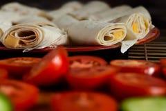 健康素食早餐概念:在红色板材的滚动的乳酪炸玉米饼用切的蕃茄和黄瓜在切板 库存照片