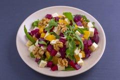 健康素食沙拉用甜菜根、绿色芝麻菜、桔子、希腊白软干酪和核桃在板材 库存图片