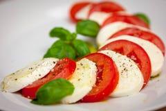 健康经典caprese沙拉-蕃茄、无盐干酪和蓬蒿 库存照片