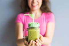健康绿色圆滑的人在妇女` s手上 素食主义者、未加工的食物、戒毒所和饮食生活方式 免版税库存图片