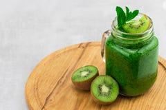 健康绿色圆滑的人用在一个瓶子杯子的菠菜有成份的 图库摄影
