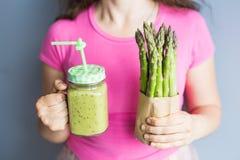 健康绿色圆滑的人用芦笋在妇女` s手上 素食主义者、未加工的食物、戒毒所和饮食生活方式 免版税库存图片