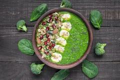 健康绿色菠菜和硬花甘蓝圆滑的人碗冠上了用香蕉 格兰诺拉麦片、石榴和chia种子 免版税图库摄影