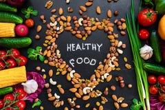 健康背景的食物 与新鲜蔬菜的健康食物概念烹调和坚果的一些亲切的类型的 图库摄影