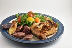 健康膳食用烘烤器草本用硬皮覆盖了鸡、多色鱼种土豆和芝麻菜沙拉用祖传遗物蕃茄和柠檬 库存图片