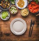 健康膳食的鲜美素食成份在碗:鹰嘴豆制成菜泥,烤菜、红色辣椒粉炖煮的食物、鲕梨和种子 图库摄影