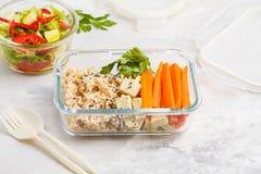 健康膳食预习功课容器用糙米、豆腐和菜 免版税库存图片