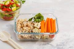 健康膳食预习功课容器用糙米、豆腐和菜 免版税库存照片
