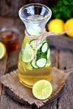 健康自创柠檬水由与冰的石灰、黄瓜和糖浆龙舌兰制成 土气样式,老木背景 免版税库存图片