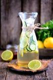 健康自创柠檬水由与冰的石灰、黄瓜和糖浆龙舌兰制成 土气样式,老木背景 免版税图库摄影