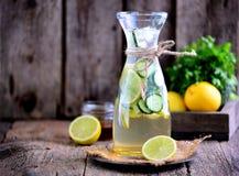 健康自创柠檬水由与冰的石灰、黄瓜和糖浆龙舌兰制成 土气样式,老木背景 库存照片