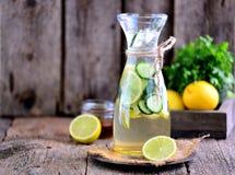 健康自创柠檬水由与冰的石灰、黄瓜和糖浆龙舌兰制成 土气样式,老木背景 库存图片