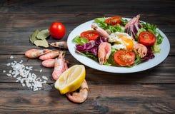 健康虾和芝麻菜沙拉用在一张木桌上的蕃茄 免版税库存图片