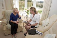 健康访客和一名有点聋患者 免版税图库摄影