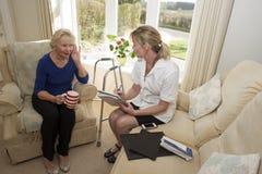 健康访客和一名有点聋患者 库存照片