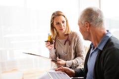 健康访客和一名老人有片剂的在家庭参观期间 免版税库存照片