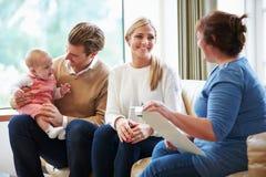 健康访客谈话与与年轻婴孩的家庭 免版税库存照片
