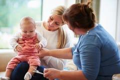 健康访客谈话与有年轻婴孩的母亲 免版税图库摄影
