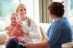 健康访客谈话与有年轻婴孩的母亲 免版税库存图片