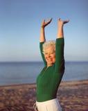 健康资深在海滩的女子实践的瑜伽 库存图片