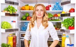 健康近妇女开放冰箱 免版税库存照片