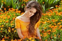 健康长的卷发。在万寿菊的美丽的深色的妇女 免版税图库摄影