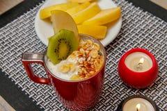 健康食品、各种各样的种子、缺一不可的谷物和干果子在酸奶 新鲜水果、苹果、猕猴桃和柿子 免版税图库摄影