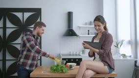 健康食品,年轻人准备吃在午餐和妇女的有用的素食主义者坐与片剂的厨房用桌 股票视频