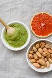 健康食品,开心果酱,被剥皮的和削皮的盐味的开心果,葡萄柚,在光的木匙子的概念 免版税库存照片