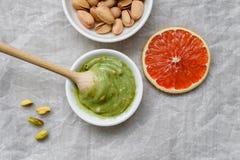 健康食品,开心果酱,被剥皮的和削皮的盐味的开心果,葡萄柚,在轻的背景的木匙子 要素 免版税图库摄影