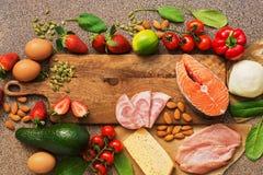 健康食物低在碳水化合物 Keto饮食概念 三文鱼,鸡、菜、草莓、坚果、鸡蛋和蕃茄,切开 免版税库存图片