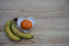 健康食物摄影图象用香蕉和一个桔子新鲜水果与拉长在微笑在爱心脏形状盘在木头 库存图片